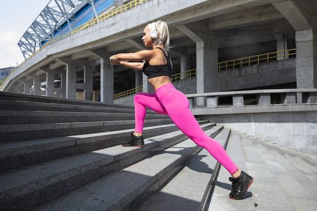Una giovane donna atletica in camicia e cuffie bianche che risolvono ascoltando la musica all'aperto della via.