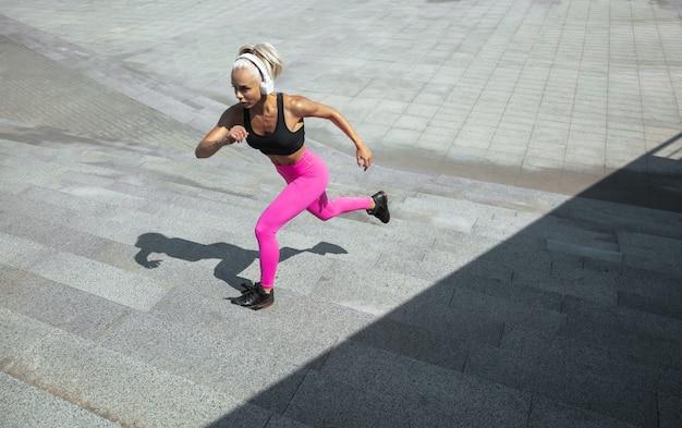 Una giovane donna atletica in camicia e cuffie bianche che risolvono ascoltando la musica all'aperto della via