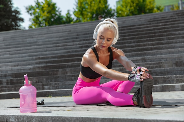 A young athletic woman in shirt and white headphones working out listening to the music at the street outdoors