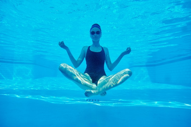 Young athletic woman sitting in lotus pose underwater in swimming pool