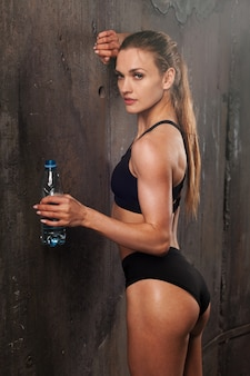Young athletic woman in sportswear drinking water