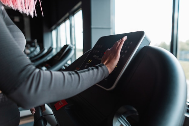 Young athletic woman starts jogging on treadmill and chooses running mode