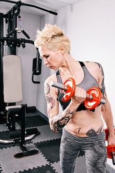Молодая спортивная (ый) женщина тренируется с гантелями в тренажерном зале. концепция фитнеса и здорового образа жизни.