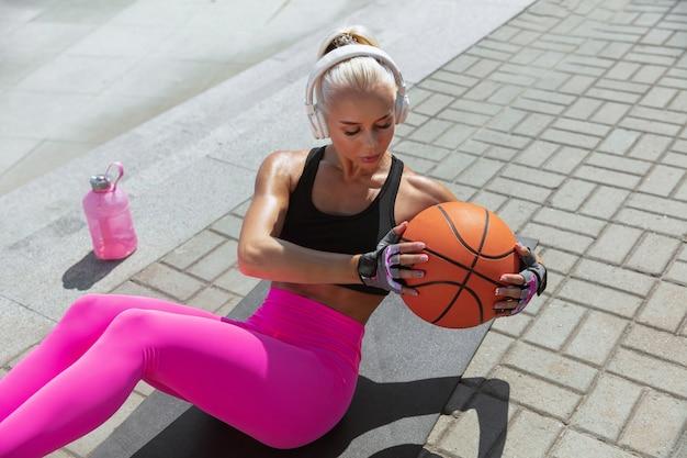 Una giovane donna atletica in formazione cuffie bianche, ascoltando la musica in strada all'aperto.