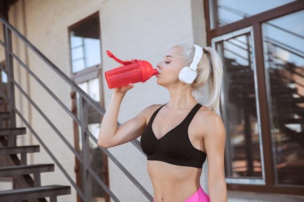 Una giovane donna atletica in cuffie bianche che risolve ascoltando la musica su una scala all'aperto. bere acqua dalla bottiglia sportiva. concetto di stile di vita sano, sport, attività, perdita di peso.