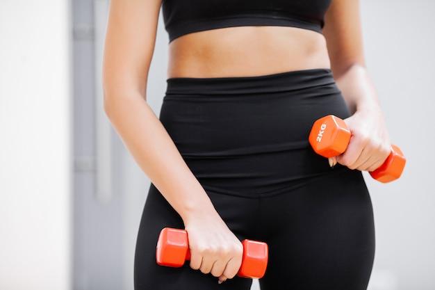 屋内でダンベルを持つ若い運動女性。ジムでのフィットネス女性のトレーニング。