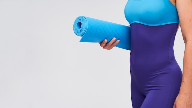 Young athletic woman with a mat for gymnastics in her hands.