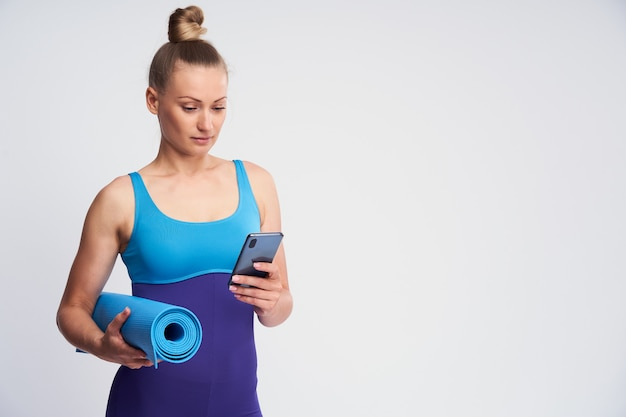 Young athletic woman with a mobile phone and a mat for gymnastics in her hands.