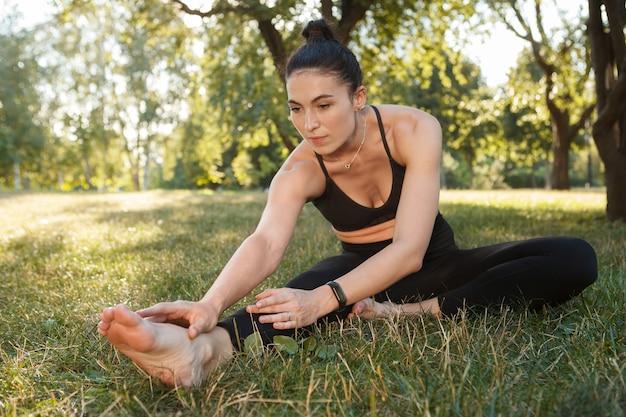 公園で運動し、芝生の上でストレッチする若いアスリート女性