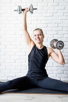 ダンベルで運動する若い運動女性