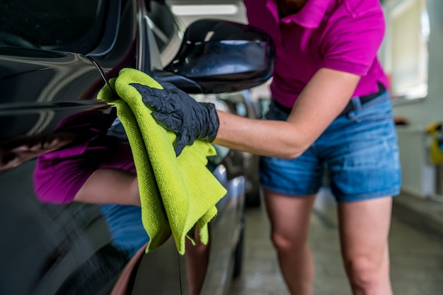 Young atractive woman polishing car body in service