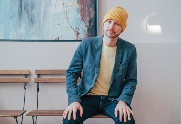 Young attractive adult bearded man hipster in yellow hat sitting on chair and looking at camera