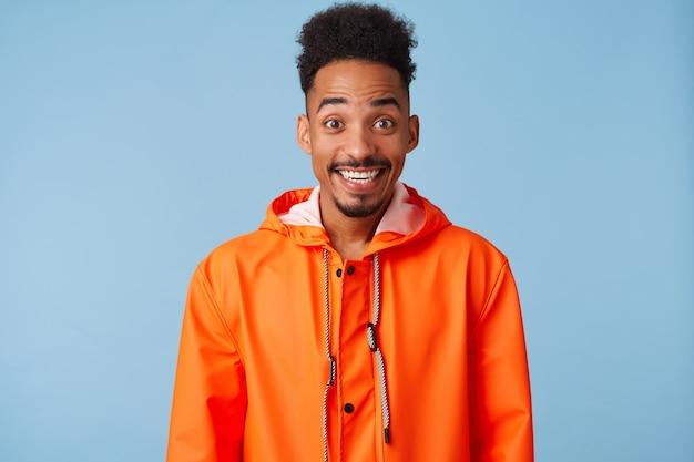 Il giovane ragazzo dalla pelle scura afroamericano attraente indossa un cappotto di pioggia arancione, si sente molto felice, sorride ampiamente.