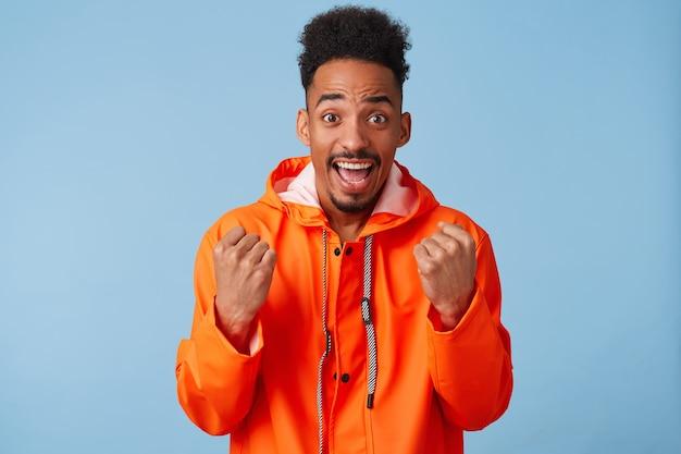 若い魅力的なアフリカ系アメリカ人の暗い肌の男は勝利を喜んで、オレンジ色のレインコートを着て、とても幸せに感じ、広く笑顔で、拳を握り締めます。