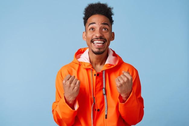 Il giovane ragazzo dalla pelle scura afroamericano attraente indossa un cappotto impermeabile arancione, si sente molto felice, sorride ampiamente, guarda in alto e stringe i pugni.