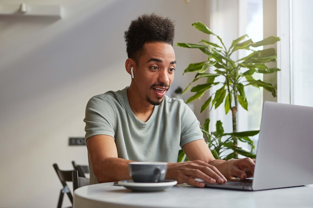 Young attractive african american happy amazed boy, sits in a cafe and works at a laptop, looks at the monitor and broadly smiling, read the article with great news.