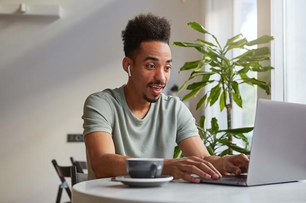 Молодой привлекательный афроамериканец доволен изумленным мальчиком, сидит в кафе и работает за ноутбуком, смотрит в монитор и широко улыбается, читает статью с отличными новостями.