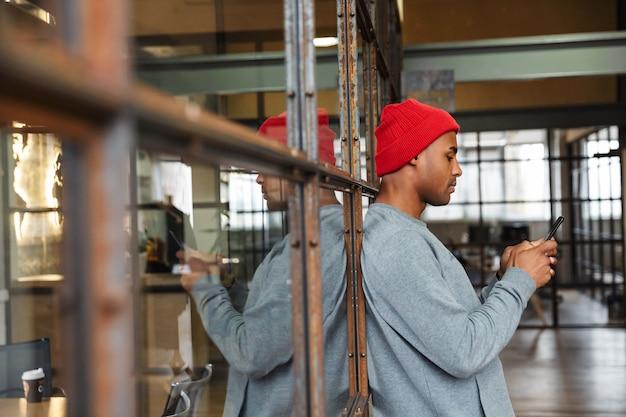 Молодой привлекательный афро-американский мужчина в шляпе держит мобильный телефон во время работы в офисе