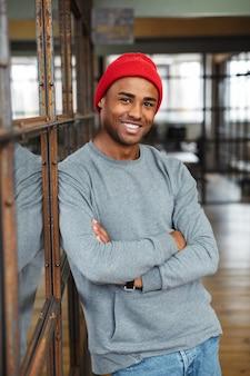 Молодой привлекательный афро-американский мужчина в шляпе, стоя со скрещенными руками во время работы в офисе