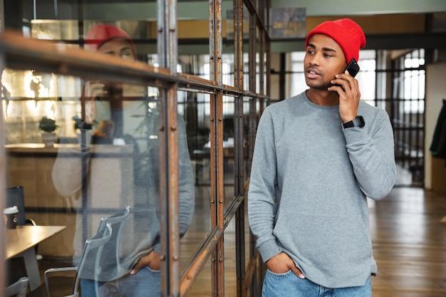 Молодой привлекательный афро-американский мужчина в шляпе разговаривает по мобильному телефону во время работы в офисе