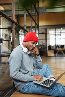 Молодой привлекательный афро-американский мужчина в шляпе с помощью портативного компьютера во время работы в офисе