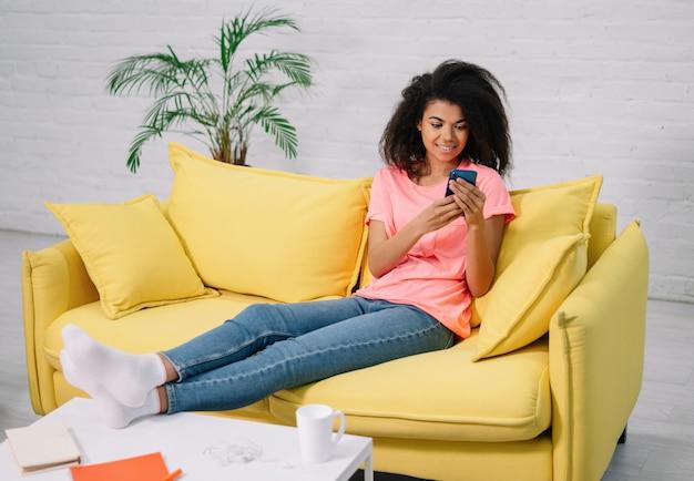 若い魅力的なアフリカ系アメリカ人女性はスマートフォンを押し、ウェブサイトで食べ物を注文し、快適な黄色のソファーに座っています。オンラインショッピングのためのモバイルアプリを使用して幸せな女の子、家にいる