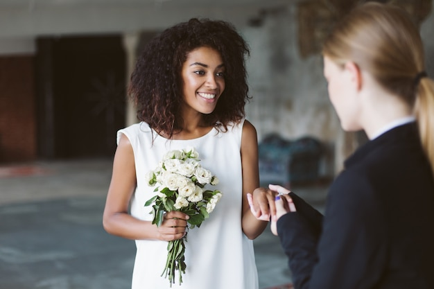 Young attractive african american woman with dark curly hair in white dress holding little bouquet of flowers in hand while joyfully spending time on wedding ceremony
