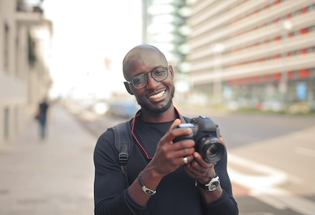 Young attractive african male photographer with a camera in a street under the sunlight