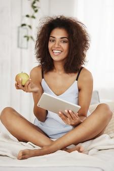 Молодая привлекательная африканская женщина в пижамах или пижамах сидя на кровати усмехаясь держащ таблетку и яблоко в утре.