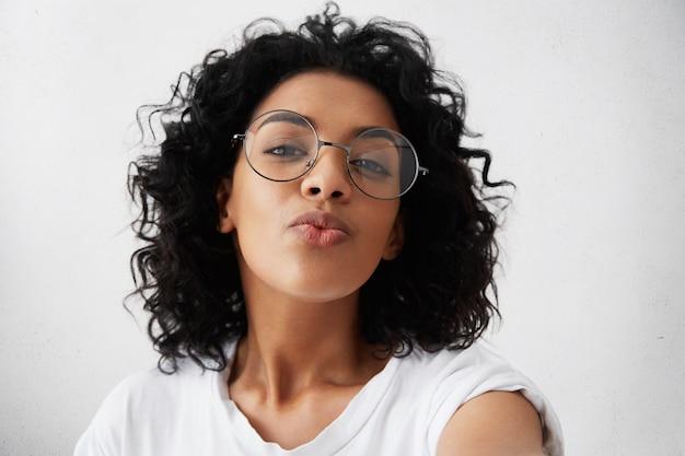 若い魅力的なアフリカ女性が彼女の唇にキスでポーズをとって、トレンディな眼鏡をかけて、自信と美しさを感じている軽薄な表情をしています。室内で楽しんでいるアフロの髪を持つ魅力的な浅黒い肌の女性