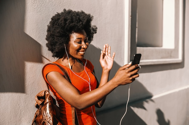 Young attractive african woman standing outdoors, having video call over smart phone and waving