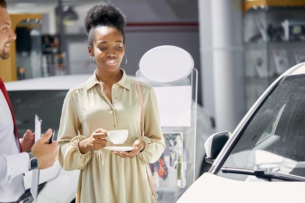 젊은 매력적인 아프리카 여자 새로운 자동차의 소유자가 되 고 즐길