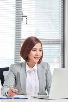 Молодая, привлекательная и уверенная деловая женщина, работающая в офисе