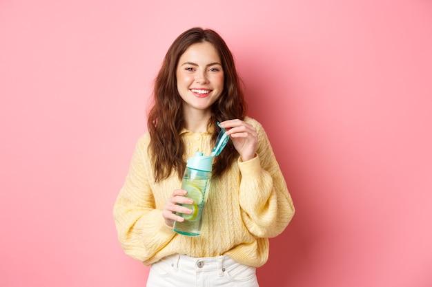 ピンクの壁にカラフルな服を着て立っているレモンを飲むスポーツドリンクとカメラのオープンウォーターボトルで笑っている若い魅力的で健康な女性