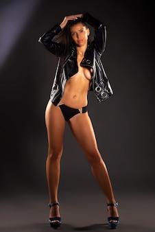 St에서 토플리스 포즈를 취하는 검은 가죽 재킷에 긴 머리를 가진 젊고 매력적이고 섹시한 모델