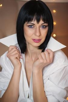 스튜디오에서 포즈를 취하는 긴 머리를 가진 젊고 매력적이고 섹시한 모델