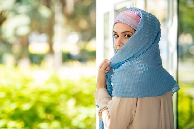 Young attractive arabian woman in hijab looking at you over her shoulder in natural environment
