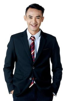 흰색 셔츠와 넥타이 손을 주머니에 넣은 검은 양복을 입은 젊은 매력적인 아시아 사업가는 고립된 흰색 배경에서 웃고 있습니다.
