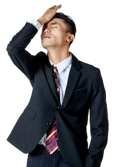 白いシャツとネクタイと黒のスーツを着てがっかりしているように見える若い魅力的なアジアのビジネスマンは、この額に手を置きます。白色の背景。孤立