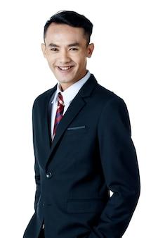흰색 셔츠와 넥타이를 매고 검은 양복을 입은 젊고 매력적인 아시아 사업가는 고립된 흰색 배경에서 웃고 있는 주머니에 손을 45도 회전합니다.