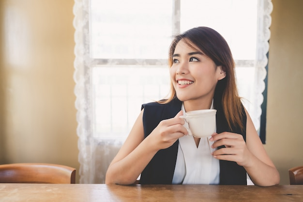 Young attractive asian business woman drinking coffee in cafe