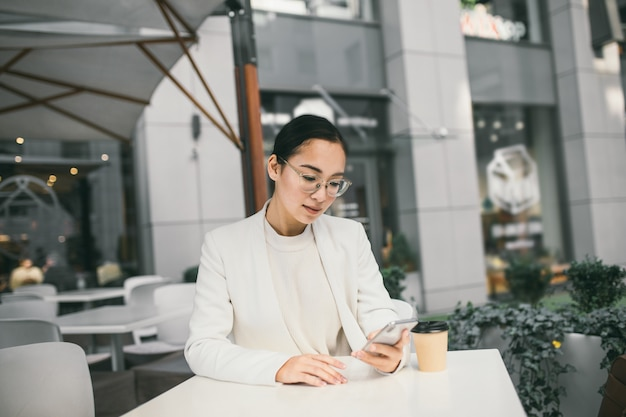 Young attractive asian business woman in glasses is sitting outside a coffee shop, drinking coffee