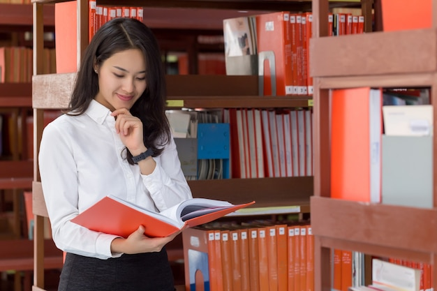 Young attractive asian business woman standing and reading book in the library