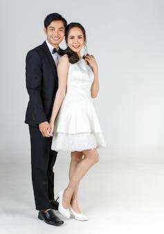 젊은 매력적인 아시아 부부, 신부 및 신랑, 흰색 웨딩 드레스를 입고 여자. 함께 서 있는 검은 턱시도를 입은 남자. 사전 웨딩 사진에 대한 개념입니다.