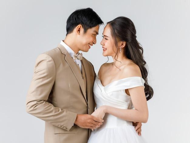 젊은 매력적인 아시아 커플, 베이지색 양복을 입은 남자, 흰색 웨딩 드레스를 입은 여자가 꽃다발을 들고 서로를 바라보고 있습니다. 사전 결혼식 사진에 대한 개념입니다.