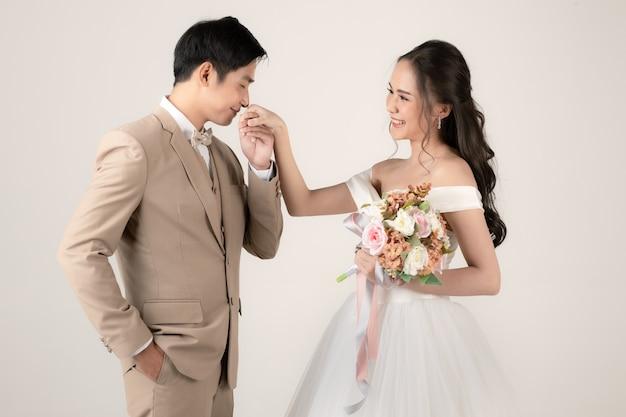 若い魅力的なアジアのカップル、ベージュのスーツを着ている男性、白いウェディングドレスを着ている女性、花の花束を持っている女性、女性の手にキスをしている男性。結婚式前の写真撮影のコンセプト。