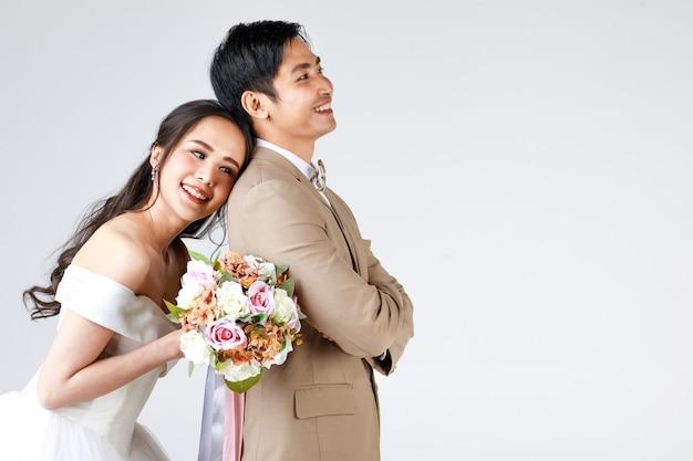 젊은 매력적인 아시아 커플, 베이지색 양복을 입은 남자, 흰색 웨딩 드레스를 입은 여자, 꽃다발을 들고 뒤에서 남자를 껴안고 있는 여자. 사전 결혼식 사진에 대한 개념입니다.