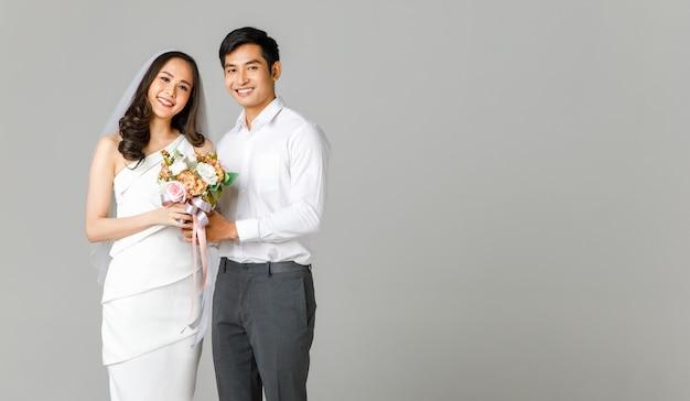 젊은 매력적인 아시아 커플, 흰 셔츠를 입은 남자, 꽃다발을 함께 들고 웨딩 베일과 함께 흰 드레스를 입고 여자. 사전 결혼식 사진에 대한 개념입니다.