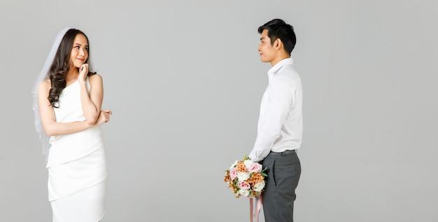 젊은 매력적인 아시아 커플, 흰색 셔츠를 입은 남자, 웨딩 베일이 떨어져 서 있는 흰색 드레스를 입은 여자. 꽃다발을 들고 있는 남자. 사전 결혼식 사진에 대한 개념입니다.