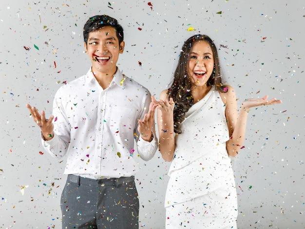 若い魅力的なアジアのカップル、白いシャツを着た男性、結婚式のベールと一緒に祝う白いドレスを着た女性。結婚式前の写真撮影のコンセプト。